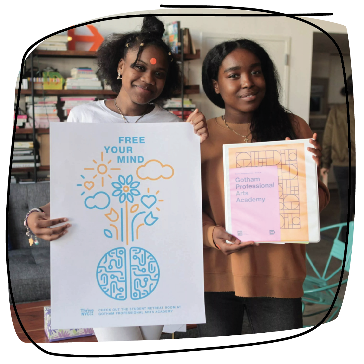 photo of two NYC students proudly holding their artwork